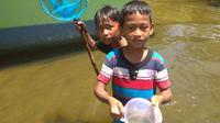 Dua anak menunjukkan ikan bethik hasil tangkapan mereka di halaman rumah. (foto : Liputan6.com / edhie)