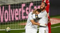 Bek Real Madrid, Sergio Ramos, merayakan gol yang dicetak Karim Benzema ke gawang Villarreal pada laga lanjutan La Liga pekan ke-37 di Estadio Alfredo Di Stefano, Jumat (17/7/2020) dini hari WIB. Real Madrid menang 2-1 atas Villarreal. (AFP/Gabriel Bouys)