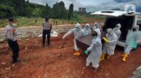 Petugas membawa peti mati berisi jenazah korban COVID-19 saat pemakaman di TPU Jombang, Tangerang Selatan, Senin (18/01/2021). Berdasarkan penuturan keluarga, keluarganya meninggal akibat terlambat penanganan karena rumah sakit rujukan COVID-19 penuh. (merdeka.com/Arie Basuki)