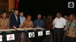Menko Bidang Kemaritiman Luhut Binsar Panjaitan dan Menristekdikti Mohamad Nasir menyaksikan MoU terkait pengembangan Stasiun Pengisian Kendaraan Listrik Umum (SPKLU) bersama produsen dan distributor mobil listrik di Jakarta, Rabu (16/10/2019). (Liputan6.com/Fery Pradolo)