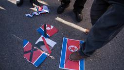 Bendera Korut diinjak pengunjuk rasa anti-Korea Utara saat menggelar aksi di pelabuhan Mukho di Donghae, Korsel (6/2). Mereka melakukan aksi menyambut rombongan seni dari Korut yang akan tampil di Olimpiade Musim Dingin Pyeongchang 2018. (AFP/Ed Jones)