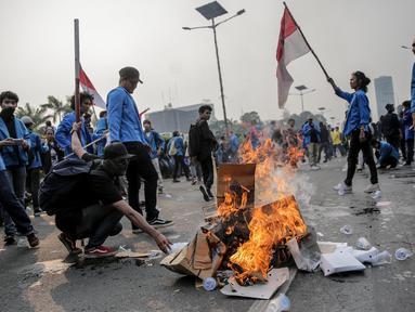 Mahasiswa peserta aksi melakukan pembakaran sejumlah kardus saat menutup tol dalam kota di depan Gedung DPR/ MPR RI, Jakarta, Selasa (24/9/2019). Demonstrasi mahasiswa di depan Gedung DPR ini di antaranya menuntut penolakan atas pengesahan sejumlah RUU kontroversial. (Liputan6.com/Faizal Fanani)