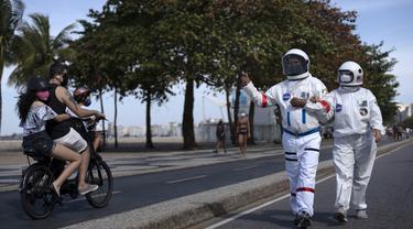 Akuntan Brasil Tercio Galdino (66) memberi isyarat jempol kepada warga yang mengendarai sepeda motor saat dia dan istrinya Alicea Galdino berjalan di sepanjang pantai Leme dengan pakaian pelindung mirip astronaut, Rio de Janeiro, Brasil, 12 Juli 2020. (Mauro Pimentel/AFP)