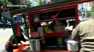 Seorang emak-emak yang juga PKL menangis saat gerobak ketopraknya dibawa oleh Satpol PP dalam sebuah razia.