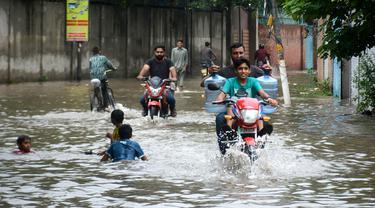 Warga mengendarai sepeda motor di jalanan yang terendam banjir setelah hujan lebat mengguyur Lahore, Punjab, Pakistan, 20 Agustus 2020. Sebanyak 18 orang tewas dan banyak lainnya terluka akibat hujan lebat di Punjab. (Xinhua/Sajjad)