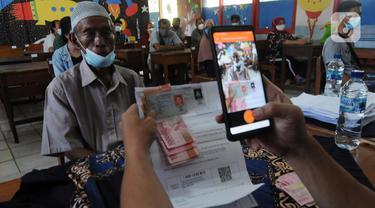 Petugas memotret warga penerima Bantuan Sosial Tunai (BST) di SDN Pondok Cabe Udik 03, Tangerang Selatan, Rabu (28/07/2021). Lebih dari dari 1800 warga mendapatkan BST yang dirapel dua bulan sekaligus dengan total Rp600ribu. (merdeka.com/Arie Basuki)