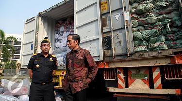 Presiden Joko Widodo berbincang dengan Dirjen Bea Cukai Heru Pambudi saat penindakan barang tekstil impor ilegal di Jakarta, Jumat (16/10/2015). Jokowi menyebut, maraknya impor tekstil ilegal merusak industri nasional. (Liputan6.com/Faizal Fanani)