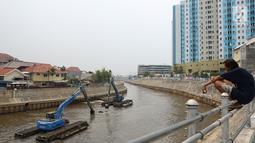 Warga melihat pengerukan endapan material lumpur dan sampah di Kali Ciliwung, Jakarta Timur, Kamis (18/10). Pengerukan lumpur dilakukan untuk antisipasi datangnya banjir saat musim hujan. (Merdeka.com/Imam Buhori)