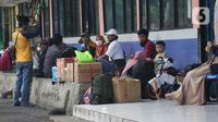 Calon pemudik menanti waktu keberangkatan di area Terminal Kampung Rambutan Jakarta, Senin (30/3/2020). Pemerintah sedang menyiapkan peraturan terkait mudik lebaran 2020 untuk mengurangi mobilitas penduduk dalam upaya pencegahan penyebaran virus Corona COVID-19. (Liputan6.com/Helmi Fithriansyah)