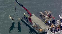 Petugas menggunakan derek dalam operasi pengangkatan bagian pesawat amfibi dari Sungai Hawkesbury, Sydney, Kamis (4/1). Bangkai pesawat jenis DHC-2 Beaver itu akan dikirim ke fasilitas yang aman guna diperiksa penyelidik. (Mick Tsikas/AAP Images via AP)