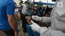 Seorang pria menjalani tes usap atau Swab Antigen di Pelabuhan Kali Adem, Jakarta, Kamis (31/12/2020). Pemeriksaan swab antigen kepada wisatawan yang akan liburan Tahun Baru di Kepulauan Seribu dilakukan untuk mencegah penyebaran COVID-19. (merdeka.com/Imam Buhori)