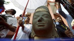 Kepala patung dewa Hindu dari abad ke-7 terlihat pada upacara di Museum Nasional Kamboja, di Phnom Penh, Kamis (21/1). Prancis mengembalikan kepala patung dewa yang disebut Harihara itu setelah diambil lebih dari 130 tahun lalu. (REUTERS/Samrang Pring)
