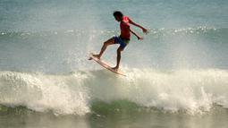 Seorang pria berselancar di pantai Kuta dekat Denpasar di pulau resor Indonesia di Bali (3/5). Pantai Kuta sering pula disebut sebagai pantai matahari terbenam (sunset beach) sebagai lawan dari pantai Sanur. (AFP Photo/Sonny Tumbelaka)