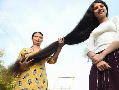 Gadis asal India, Nilanshi Patel (17) berpose dengan ibunya, Kaminibenat di kota Modasa, sekitar 110 Km dari Ahmedabad, Minggu (19/1/2020). Patel mendapat penghargaan Guinness World Record sebagai remaja yang punya rambut terpanjang di dunia dengan panjang hingga 190 cm. (SAM PANTHAKY/AFP)