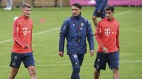 Gelandang baru Bayern Munchen, Michael Cuisance (kiri) berjalan dengan pelatih Niko Kovac (tengah) dan Philippe Coutinho bersiap mengikuti latihan di Munich, Jerman (20/8/2019).  (Sven Hoppe/dpa via AP)