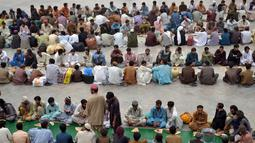 Mereka duduk berbaris dengan rapi dan saling berhadapan. Panjang barisan bisa mencapai 10 meter. Ratusan orang selalu berkumpul hampir setiap hari selama Ramadan, Quetta, Pakistan, Rabu (2/7/2014) (AFP PHOTO/BANARAS KHAN)