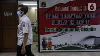 Pegawai Badan Kepegawaian Daerah DKI Jakarta berjalan di Kantor Balai Kota DKI Jakarta, Kamis (11/2/2021). Kementerian PANRB secara resmi melarang seluruh ASN bepergian ke luar kota saat libur Imlek guna mencegah penyebaran dan penularan COVID-19. (Liputan6.com/Johan Tallo)