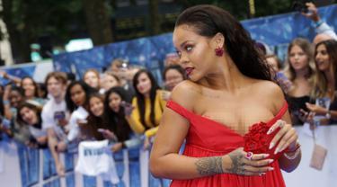 Penyanyi yang juga aktris, Rihanna saat menghadiri pemutaran perdana film 'Valerian and the City of Thousand Planets' di London, Senin (24/7). Penyanyi berusia 29 tahun itu mengenakan gaun merah menakjubkan dari Giambattista Valli. (Joel Ryan/Invision/AP)
