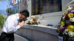 Pejabat konsulat Jepang berdoa di Monumen Bom Bali, Kuta, dekat Denpasar pada Sabtu (12/10/2019). MeMperingati 18 tahun peristiwa bom Bali yang terjadi pada 12 Oktober 2002, wisatawan dan kerabat korban mengunjungi tugu peringatan untuk berdoa dan tabur bunga. (SONNY TUMBELAKA / AFP)