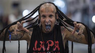 Seniman tato asal Brasil, Dark Virus berpose memamerkan tato, tindikan, dan lidahnya yang dimodifikasi dalam acara Sao Paulo Tattoo Week, Brasil, Jumat (25/10/2019). Sao Paulo Tattoo Week adalah acara tahunan yang diikuti pecinta tato dari seluruh dunia. (AP Photo/Andre Penner)