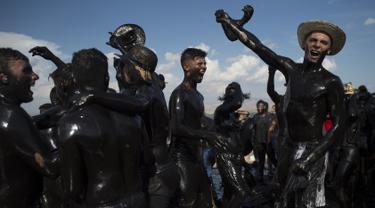 Para peserta dengan tubuh dilumuri minyak hitam mengikuti Festival Tradisionlal Cascamorras di Baza, Granada, Spanyol (6/9/2019). Festival ini diadakan setiap tanggal 6 September dan telah berlangsung selama 500 tahun terakhir. (AFP Photo/Jorge Guerrero)