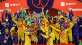 Para pemain Barcelona memegang trofi saat mereka merayakan kemenangan setelah memenangkan final Copa del Rey Spanyol 2021 melawan Athletic Bilbao di stadion La Cartuja di Seville, Spanyol, Minggu (18/4/2021). Barcelona menang atas Athletic Bilbao 4-0.  (HANDOUT / RFEF / AFP)