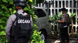 Personel Gegana Polda Metro Jaya memeriksa Sebuah mobil yang terparkir di area gereja katedral, Jakarta, Rabu (24/12/2014). (Liputan6.com/Faizal Fanani)