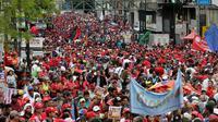 Pendukung Presiden Venezuela, Nicolas Maduro ikut ambil bagian dalam unjuk rasa memperingati May Day 2016 atau Hari Buruh Sedunia di Caracas, Minggu (1/5). Di beberapa negara, peringatan buruh sempat diwarnai dengan aksi bentrok. (REUTERS/Marco Bello)