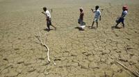 Para pekerja berjalan di atas danau yang telah kering di India (Foto: Reuters).