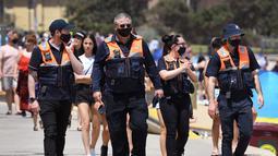 Petugas keamanan berpatroli di Pantai St Kilda Melbourne, Australia (3/11/2020). Negara bagian Victoria di Australia mencatat nol kasus penularan virus corona (Covid-19) selama empat hari berturut-turut setelah berjuang melawan gelombang kedua wabah pandemi. (AFP/William West)