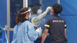 Seorang petugas medis mengambil sampel dari petugas polisi selama pengujian COVID-19 di Badan Kepolisian Metropolitan Seoul di Seoul, Korea Selatan, Rabu, (19/8/2020). (AP Photo / Ahn Young-joon)