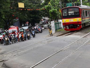Kereta melintas di kawasan Lenteng Agung, Jakarta, Selasa (13/3). Untuk mengurai kemacetan imbas antrian kendaraan berputar balik di pintu kereta IISIP, Pemprov DKI berencana membangun flyover U-Turn di kawasan tersebut. (Liputan6.com/Immanuel Antonius)