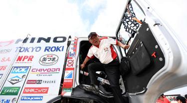Pembalap Hino Yoshimasa Sugawara dari Jepang keluar dari truknya saat melakukan pemeriksaan teknis jelang Reli Dakar 2018 di Lima, Peru (3/1). Hino satu-satunya brand truk asal Jepang yang ambil bagian dalam edisi ke-40 Reli Dakar. (AFP Photo/Franck Fife)