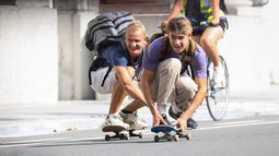 Orang-orang bermain papan luncur di sebuah jalan dalam acara Hari Minggu Bebas Kendaraan Bermotor (Car Free Sunday) di Brussel, Belgia, pada 20 September 2020. (Xinhua/Zheng Huansong)