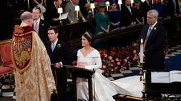 Putri Eugenie dan Jack Brooksbank saat melangsungkan proses pemberkatan nikah di Kapel St. George, Windsor Castle, London, Inggris,  Jumat (12/10). Eugenie menikahi Jack yang bekerja sebagai duta merek tequila. (Danny Lawson/Pool via AP)