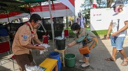 Warga mencuci tangan sebelum melakukan pemungutan suara pada Pilkada Tangerang Selatan di TPS 49 Cendana Residence, Pondok Benda, Pamulang, Rabu (9/12/2020). TPS 49 pada Pilkada Serentak 2020 mengusung tema Rindu Sekolah Lagi (Kisah-Kasih di Sekolah). (Liputan6.com/Fery Pradolo)