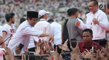 Ustaz Yusuf Mansur bersalaman dengan pendukung pasangan Capres dan Cawapres nomor urut 01, Jokowi - Ma'ruf Amin saat mengikuti kampanye akbar bertajuk 'Konser Putih Bersatu di Stadion Gelora Bung Karno (SGBK), Jakarta, Sabtu (13/4). (Kapanlagi.com/Budi Santoso)