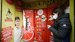 Seorang wanita menunggu pesanannya di mesin penjual pizza otomatis, yang pertama dari jenisnya di pusat kota Roma, pada 29 April 2021. Mesin penjual otomatis ini mampu menguleni adonan, membumbui, memasak, dan menyajikan pizza dalam kotak karton hanya dalam waktu tiga menit. (Filippo MONTEFORTE/AFP)