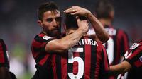 Pemain AC Milan, Giacomo Bonaventura bersama rekan setimnya, Fabio Borini merayakan gol ke gawang Bologna dalam lanjutan pekan ke-16 Liga Italia di Stadion San Siro, Senin (11/12). AC Milan menang tipis 2-1 atas Bologna. (AFP PHOTO / MARCO BERTORELLO)