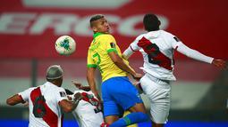 Pemain Brasil Richarlison (tengah) berebut bola dengan pemain Peru Luis Abram (kanan) pada pertandingan kualifikasi Piala Dunia 2022 di National Stadium, Lima, Peru, Selasa (13/10/2020). Brasil menang 4-2 dengan lewat hattrick dari Neymar. (Daniel Apuy, Pool via AP)