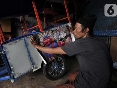 Asep saat hendak menempelkan stiker ondel-ondel pada bodi odong-odong buatannya di Jakarta, Rabu (30/10/2019). Industri rumahan milik Asep Kohar (48) itu sudah 8 tahun memproduksi odong-odong, baik jenis mainan anak maupun kereta mini yang terdiri atas 3 rangkaian. (merdeka.com/Iqbal S. Nugroho)