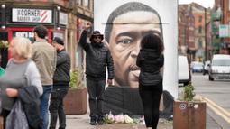 Warga berpose bersama mural George Floyd di Manchester tengah, Inggris (4/6/2020). George Floyd tewas kehabisan napas saat dalam penahanan pihak kepolisian Negara Bagian Minnesota, wilayah Midwest Amerika Serikat, pada pekan lalu. (Xinhua/Jon Super)