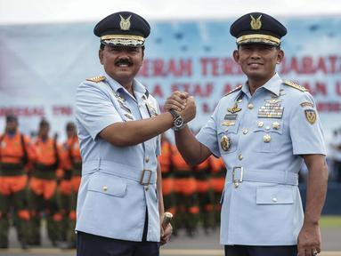 Panglima TNI Marsekal Hadi Tjahjanto (kiri), KSAU Marsekal TNI Yuyu Sutisna bersalam komando usai mengikuti upacara serah terima jabatan KSAU di Lapangan Udara Halim Perdanakusuma, Jakarta, Jumat (19/1). (Liputan6.com/Faizal Fanani)