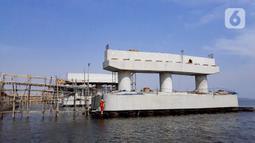 Pekerja menyelesaikan pembangunan jembatan penghubung Dadap Tangerang-Pulau C di Kamal Muara, Penjaringan, Jakarta Utara, Minggu (17/11/2019). Pembangunan jembatan tersebut menyulitkan transportasi nelayan karena perairan menjadi sempit dan laut menjadi dangkal. (merdeka.com/Iqbal Nugroho)