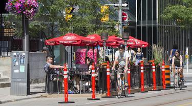 Pengendara sepeda melewati area makan terbuka sebuah restoran di Toronto, Kanada, 18 Juli 2020. Kota Toronto meluncurkan program CafeTO yang memungkinkan restoran dan bar memperluas area makan terbuka mereka guna melayani lebih banyak pelanggan dengan aman selama pandemi COVID-19. (Xinhua/Zou Zheng)