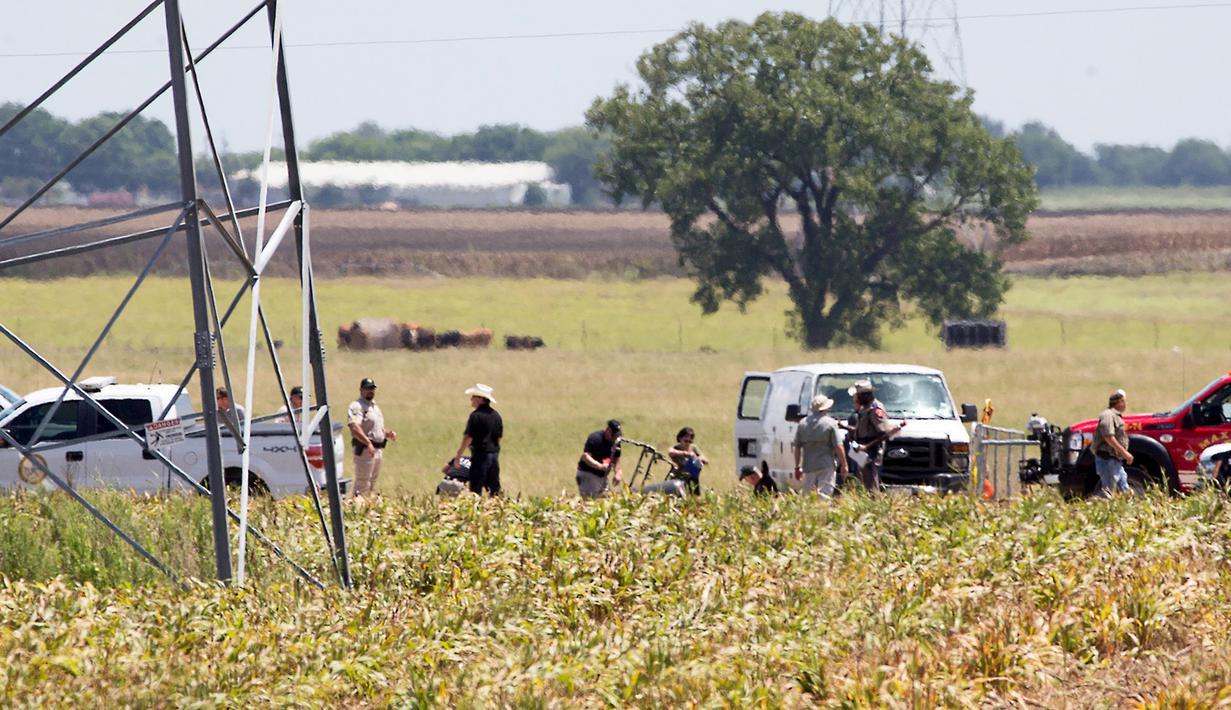 Bingkai parsial dari balon udara yang terbakar terlihat di areal padang rumput sementara penyidik melakukan penyisiran di lokasi jatuhnya balon udara tersebut, di Maxwell, wilayah Texas, Sabtu (30/7). (Ralph Barrera/Austin American-Statesman/via REUTERS)