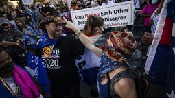 Seorang pendukung Presiden Donald Trump (kiri) dan seorang pendukung mantan Wakil Presiden Joe Biden (kanan) saling bertukar topi saat yang lain merayakan hasil Pilpres Amerika Serikat di Black Lives Matter Plaza, dekat Gedung Putih di Washington, Minggu (8/11/2020). (Samuel Corum/Getty Images/AFP)