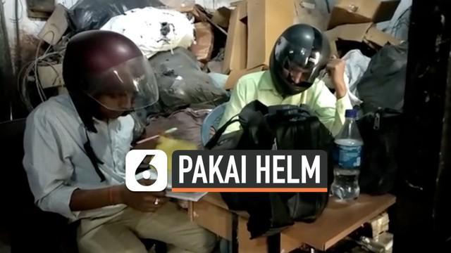 Pegawai kantor pemerintahan India menggunakan helm motor saat bekerja. Ini dilakukan agar kepala mereka tetap aman saat bekerja karena gedung kantor yang rusak.