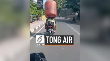Seorang pria memakai tong air diatas kepalanya saat mengendarai sepeda motor.