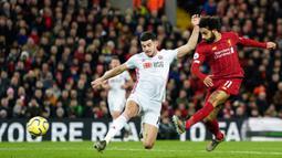 Pemain Sheffield United David McGoldrick (kiri) mencoba menghalau tendangan pemain Liverpool Mohamed Salah pada pertandingan lanjutan Liga Inggris di Anfield Stadium, Liverpool, Inggris, Kamis (2/1/2020). Liverpool menang 2-0. (AP Photo/Jon Super)